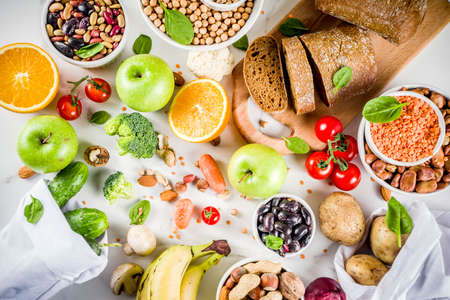 Foto per Healthy food. Selection of good carbohydrate sources, high fiber rich food. Low glycemic index diet. Fresh vegetables, fruits, cereals, legumes, nuts, greens. White marble background copy space - Immagine Royalty Free