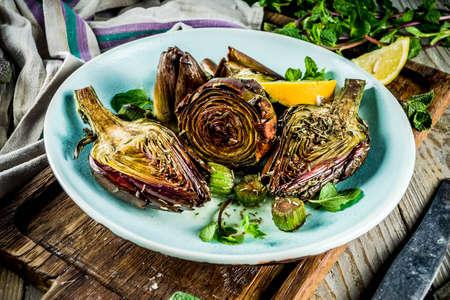 Foto de Cooked baked artichoke, alla romana, grilled artichoke flowers with olive oil, lemon, garlic, mint  and spices. Copy space - Imagen libre de derechos