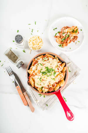 Photo pour Baked creamy pasta casserole, mac and cheese with minced meat, italian ground beef bolognese casserole, dark blue concrete background copy space - image libre de droit