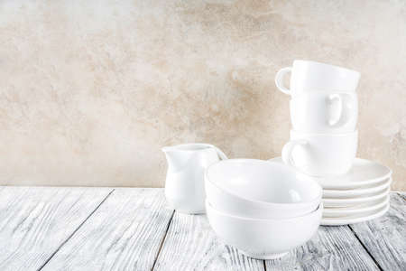 Foto de Assortment stack clean empty new white kitchen utensils, plates, bowls, cups mugs. On a white concrete background - Imagen libre de derechos