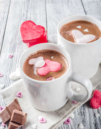 Photo pour Valentines day treat ideas, two cups hot chocolate drink with marshmallow hearts red pink white color with chocolate pieces, sugar sprinkles, old wooden background copy space top view - image libre de droit