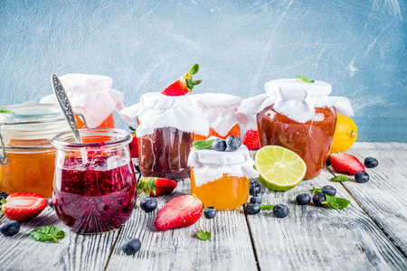 Foto de Assortment of various seasonal berry and fruit jams in jars on wooden table. Copy space - Imagen libre de derechos