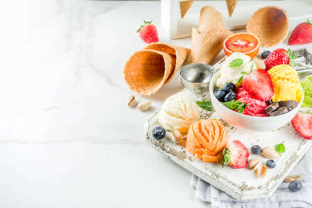 Photo for Colorful fruit and berry, nut, chocolate and vanilla ice cream, with waffle ice-cream cones, with fresh fruit and berries, top view copy space white marble background - Royalty Free Image