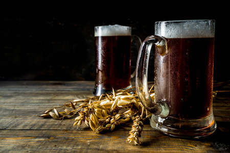 Foto de Two Homemade craft beer mugs, dark wooden background copy space - Imagen libre de derechos