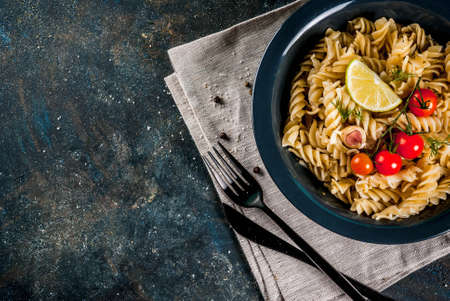 Photo pour Classic italian pasta fusilli with pesto sauce, tomatoes, lime and fresh herbs in dark bowl, dark blue background  copy space top view - image libre de droit