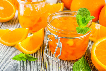 Photo pour Homemade orange jam, with fresh sliced oranges and mint leaves, white wooden background copy space - image libre de droit