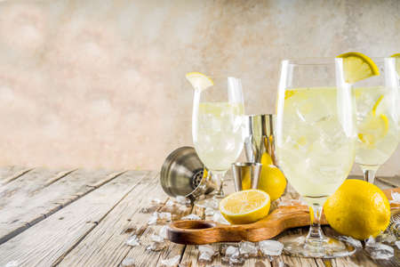 Photo pour Trendy summer cold drink. St Germain French Spritz cocktail with lemon slices, old rustic wooden background copy space - image libre de droit