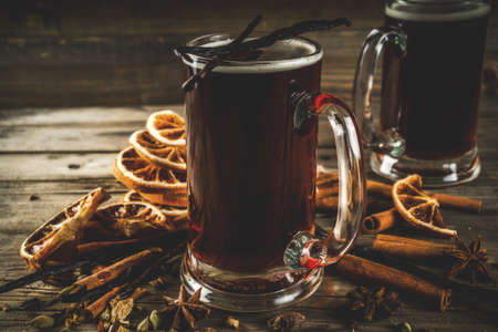Photo pour Hot beer with spices - vanilla, cinnamon, anise, citrus. Mulled dark beer drink. Dark wooden background copy space - image libre de droit