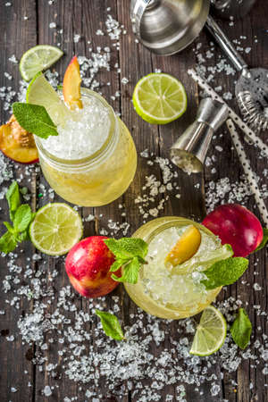 Photo pour Summer iced peach tea with mint, lime and crushed ice, wooden background copy space - image libre de droit