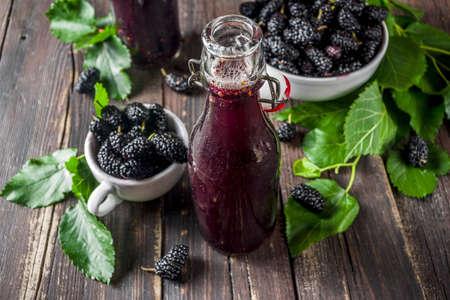 Foto de Mulberry Shrub, Juice or  liqueur in glass bottles, with fresh mulberries, rustic wooden background copy space - Imagen libre de derechos