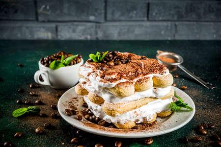 Foto de Homemade italian dessert tiramisu on plate, with cocoa and coffee beans, decorated with mint, dark green background copy space - Imagen libre de derechos
