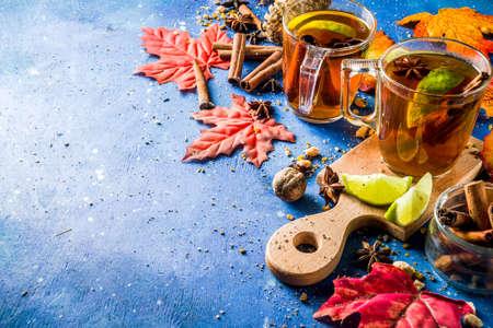 Foto de Hot spicy autumn tea with cinnamon, anise, lemon, with autumn decoration, leaves and spices - Imagen libre de derechos