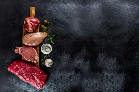 Foto de Various meat types. Red beef meat, pork steak, chicken breast filet, liver pork heart, with spices on black stone concrete background top view copy space - Imagen libre de derechos