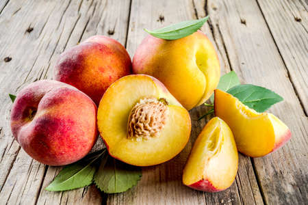 Photo for Fresh organic peaches, whole and sliced, with leaves, on rustic wooden background - Royalty Free Image