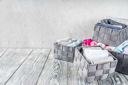 Photo pour House cleaning concept. Vertical tidying up storage. Marie Kondo tidying method. Neatly folded clothes in the organizer boxes for wardrobe. Wooden background copy space above - image libre de droit