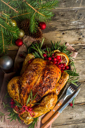 Foto de Traditional Christmas and Thanksgiving roasted whole chicken with fruit and rosemary. Rustic wooden christmas table, with xmas tree branches and decorations copy space - Imagen libre de derechos