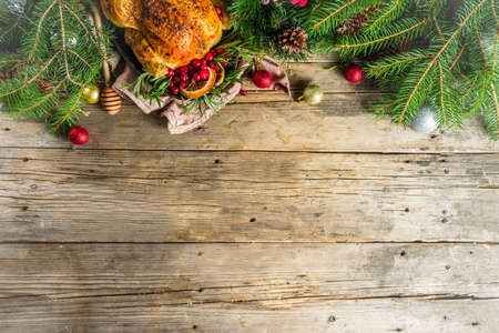 Photo pour Traditional Christmas and Thanksgiving roasted whole chicken with fruit and rosemary. Rustic wooden christmas table, with xmas tree branches and decorations copy space - image libre de droit