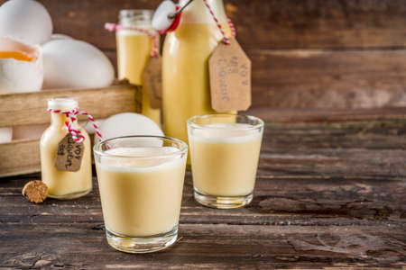 Photo for Traditional Italian Vov eggs liquor. German Egg Liqueur Eierlikor. In different bottle and shot glasses, Wooden background copy space - Royalty Free Image