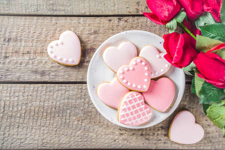Photo pour Valentine day greeting background with red rose flowers and pink glazed heart shaped cookies wooden background copy space - image libre de droit