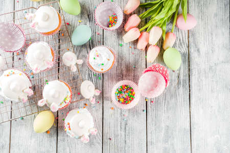 Photo pour Easter kids party treat. Festive Easter food. Homemade cupcakes with cream and marshmallow cute bunny rabbits with paws. On a white wooden table, top view copy space - image libre de droit
