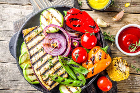 Photo pour Hot vegetable salad. Set different grilled vegetables on a plate. Vegan barbeque picnic set, with asparagus, tomatoes, mushrooms, peppers, corn and sauces - image libre de droit