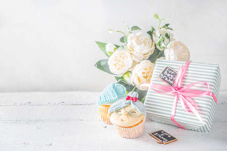 Photo pour Grandparents Day holiday concept, Grandmother and Grandfather Day greeting background. Sweet homemade cupcakes for grandma and grandpa, with I love you Granny text inscription. With gifts and flowers - image libre de droit