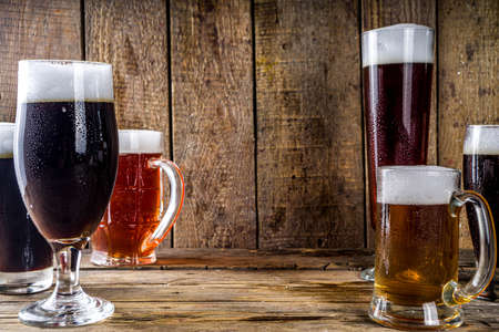 Different sorts of craft beer on wooden bar background. Set of various beer glasses and mugs. Beer tasting concept