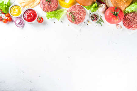 Cooking burger background. Set various cheeseburger and beefburger ingredients - bun, tomatoes, onion, lettuce, sauces, cheese and raw burger cutlets, ready for barbecue grill. Burger bbq party fest concept, top view copy spaceの素材 [FY310152080185]