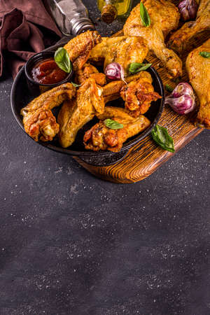 Photo pour Grilled chicken legs and wings, with herbs, spices, garlic and barbeque sauce, dark concrete table background copy space top view - image libre de droit
