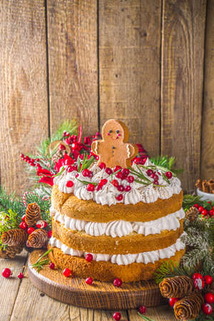 Photo for Festive Christmas gingerbread cake with whipped cream cheese, decorated cranberry and gingerbread cookies, wooden background with christmas decor copy space - Royalty Free Image