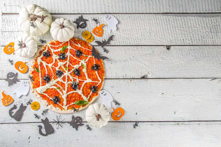 Photo pour Halloween funny pizza. Halloween party recipe, Creative idea for Halloween pizza`s with ham and cheese ghosts, monster, spiders, white wooden background with Halloween decorations - image libre de droit