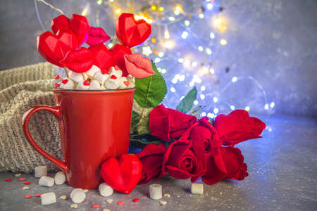 Photo pour Valentine`s day sweets concept, festive holiday background with hot chocolate red cup and set of red hearts sweets on sticks in cup, with red roses and bokeh lights effect - image libre de droit