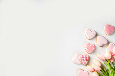 Photo pour Homemade pick sugar glazed Valentine day cookies. Valentine heart shaped bakings. White stone background copy space top view - image libre de droit