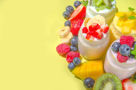 Photo for Set of various fruit and berry yogurts in glass jars. Variety healthy Breakfast yoghurt with blueberry, strawberry, mango, kiwi, raspberry, trendy bright yellow background with hard light dark shadows - Royalty Free Image