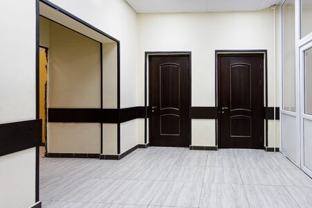 Photo pour An empty corridor in a modern office building. A hall with light walls and brown doors. - image libre de droit