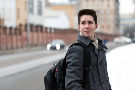 Photo pour Young free beautiful fashionable guy dressed in a coat walking with a backpack on a city street to go on a trip or to study, urban style - image libre de droit