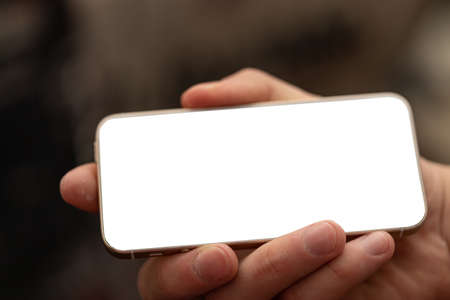 Cropped shot view of man hands holding smart phone with blank copy space screen for your text message or information content