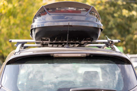 Photo pour Assembled and closed, roomy roof rack or roof box for the safety of things against a blurred background of green leaves. Back view. A family vacation trip - image libre de droit