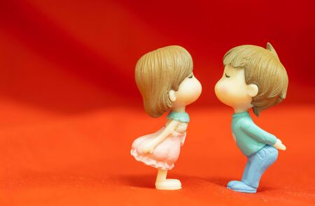 The Miniature Couple dolls Boy and Girl Romantic Kiss on Red Background for valentine\'s Day Concept