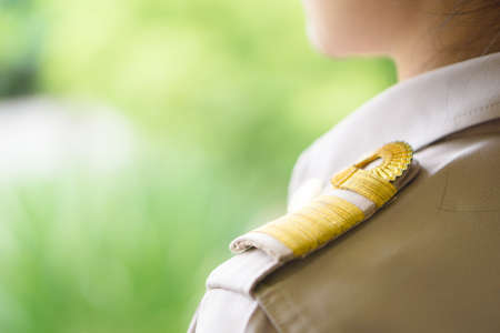 Thai teachers in official uniform focus on golden stripe shoulder accessory