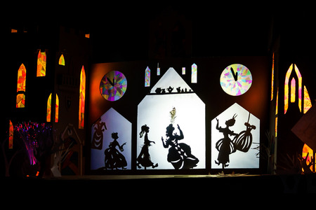 Shadows theater view. Illuminated figures over the screen