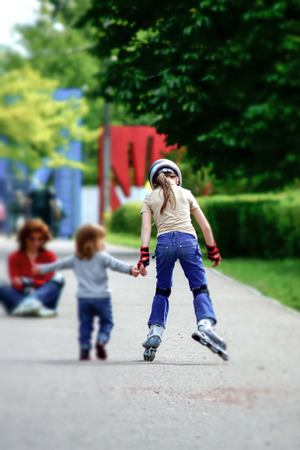 Young girl skating with little syster in a park