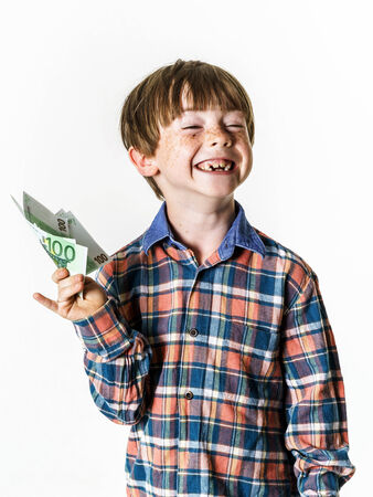 Happy red-haired boy with money in his hand