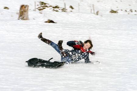 Photo pour YTeenage girl falling down from sleds, winter snowy weather - image libre de droit