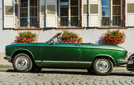 Beautiful retro green car on the street, sunny day, France