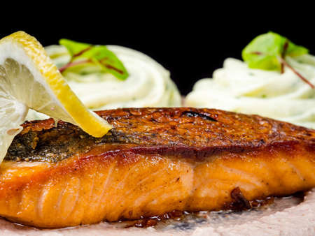 Photo pour Fried salmon, red fish, with Georgian sauce. Isolated on black background. - image libre de droit