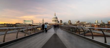 Commuters crossing the Millenium Bridge walking towards St Pauls Cathedral