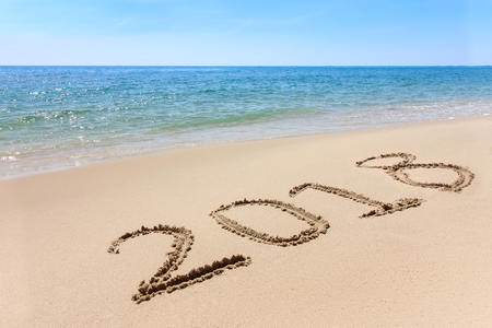 Photo pour Year 2018 written at the sand beach with sea wave water - image libre de droit