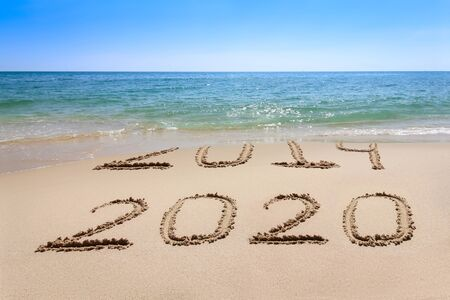 Photo for Year 2020 written at the sand beach with sea wave water - Royalty Free Image