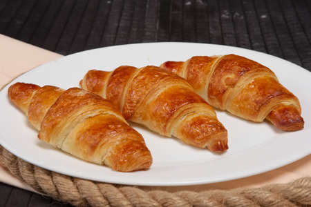Fresh baked croissants on plate
